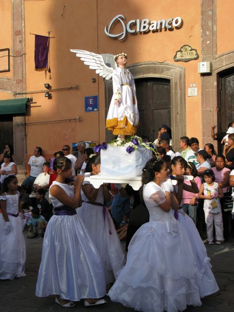 Young girls in white, carrying angels Friday Evening Procession