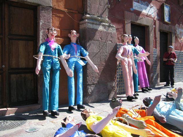 Paper mache Judas figures lined up in the Jardin
