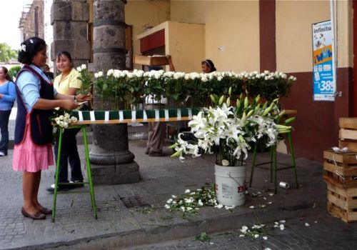 Flower shop at the market making an altar of white roses to be carried in the procession